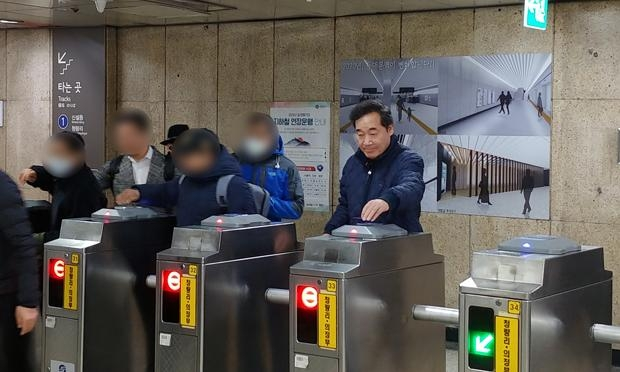 이낙연이 서민들을 응시하지 않은채 홀로 왼쪽에 교통카드를 태그하여 지하철을 한번도 안타봤음을 보여주고 있다.